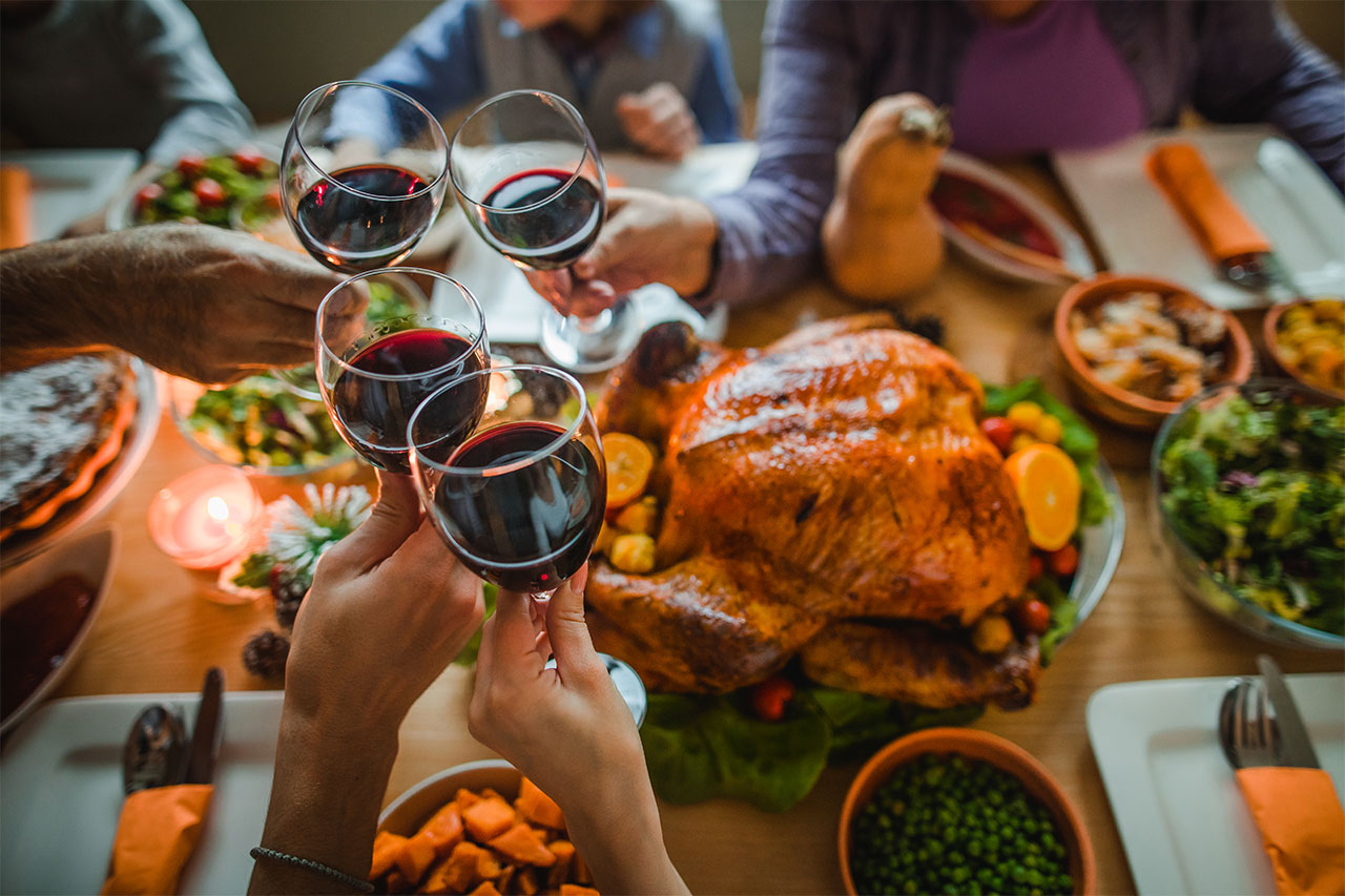 close-up shot of friends toasting wine glasses with a festive spread of holiday food on the table
